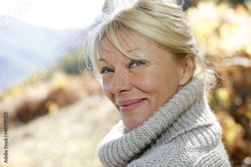 Portrait of senior woman leaning against tree
