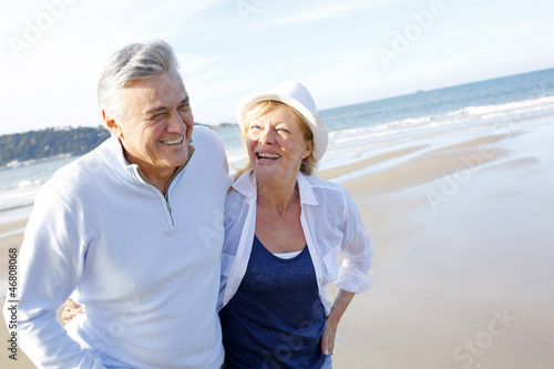 Senior couple walking on the beach in fall season
