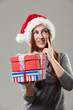 Beautiful woman in Santa hat with gifts