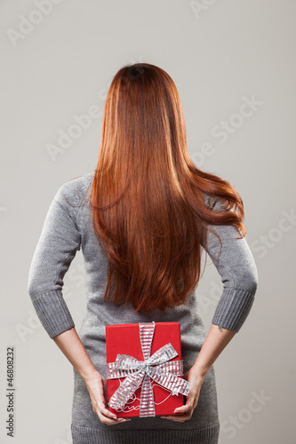 Woman hiding a gift behind her back