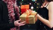 young man and woman exchanging of gifts at party