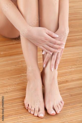 Well-groomed hands on female feet