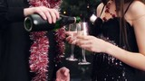 young couple with glasses and wine bottle at christmas party