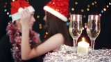 Young couple at christmas party, wine glasses at foreground