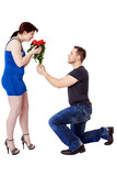 Man kneels in front of the woman and gives her flowers