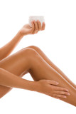 Woman applying body lotion on leg