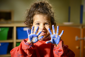 Happy little girl painting with hands in kindergarten