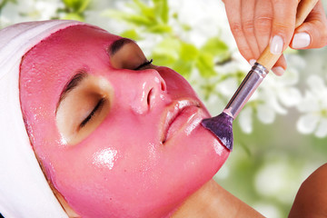 Young beautiful woman with cosmetic fruit facial mask at beauty