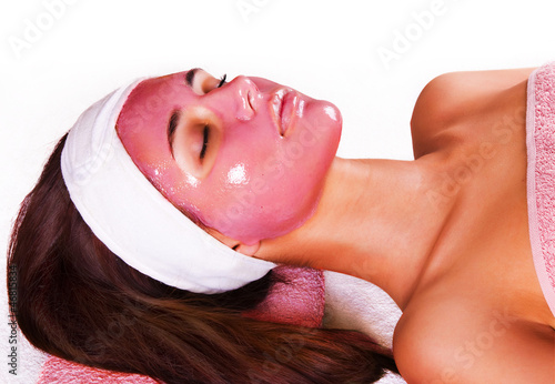 Young beautiful woman with moistening fruit facial mask at beaut