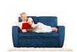 Young woman lying on a sofa reading a book