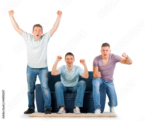Young men sitting on a sofa cheering, on white background