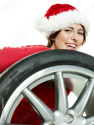 Miss santa behind a tire looking forward to christmas