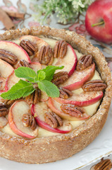 cheesecake with apples and caramelized pecans closeup