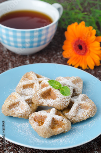 Waffles sprinkled with powdered sugar and black tea selective fo