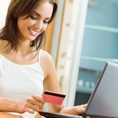 Young woman paying by plastic card, at home