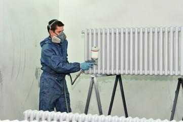 Worker painting white radiator.