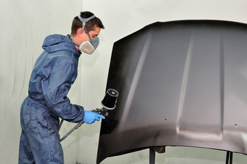 Worker painting car parts in black.
