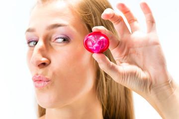 Junge Frau mit Kondom - HIV Prävention