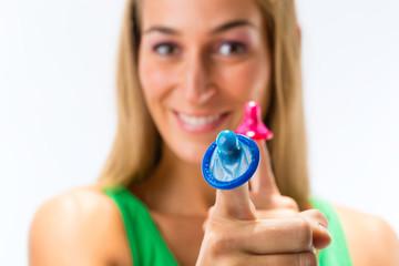 Junge Frau mit zwei Kondomen - HIV Prävention
