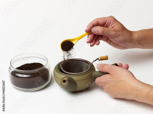 Person's hand preparing tea