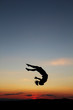 silhouette of female gymnast doing a somersault in sunset
