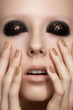 Model with bright glitter on eyelids, perfect beige nails polish