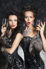 Fashion women drinking champagne in nightclub. Merry Christmas!