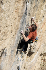 Rock climber struggling to make next movement