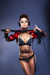 Sexy fetish woman dj in lingerie holding whip with headphones