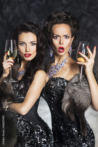 Fashion women drinking champagne in nightclub. Merry Christmas!