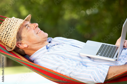 Senior Man Relaxing In Hammock With Laptop