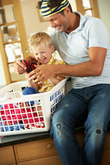 Father And Son Sorting Laundry Sitting On Kitchen Counter