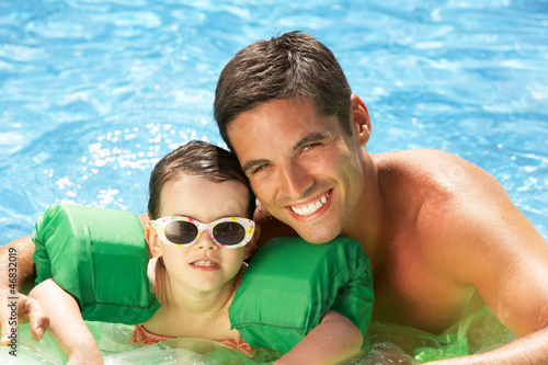 Father And Daughter With Armbands In Swimming Pool