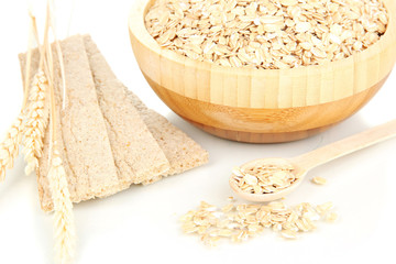 wooden bowl full of oat flakes with wooden spoon, spikelets and