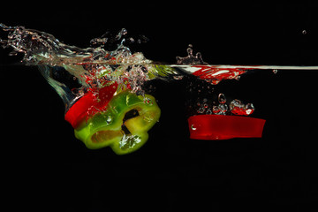 Slices of red and green peppers falling into water with splash