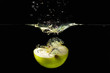 Halved fresh green apple falling into the water with a splash