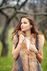 Portrait of beautiful young woman in to fur