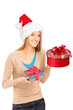 A happy female with christmas hat holding gifts in her hands