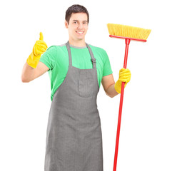A male cleaner posing with brush and giving thumb up