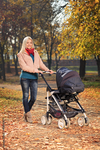 Mother pushing a baby stroller in a park in autumn