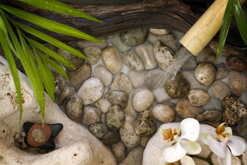 Falling water on stones spa concept with orchids and bamboo