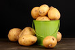 Ripe potatoes in pail on wooden table on black background