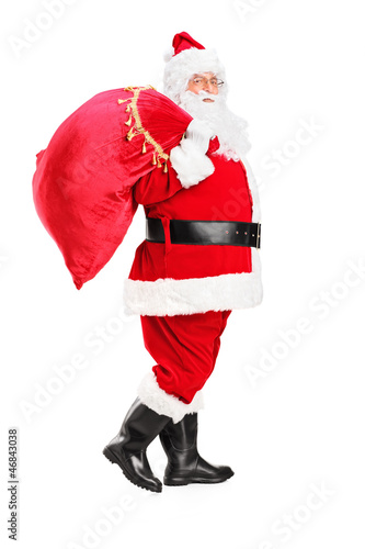 Santa Claus walking with bag full of gifts og his back