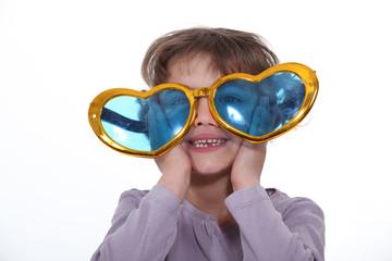 Little girl wearing heart-shaped sunglasses