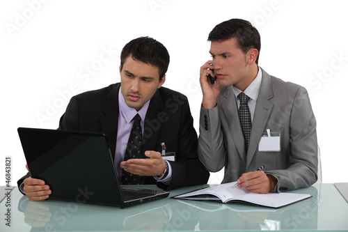Two businessmen arguing at a desk