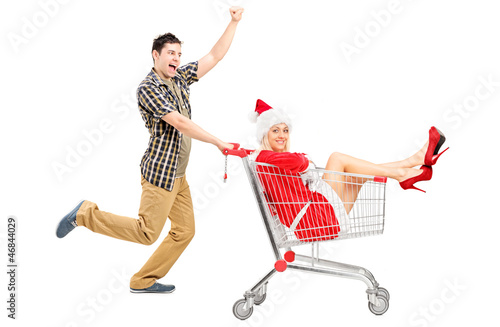Guy pushing a woman wearing christmas costume in a shopping cart