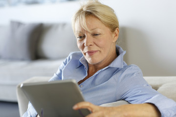 Senior woman using electronic tablet in sofa