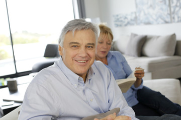 Smiling senior man sitting in couch, wife in background