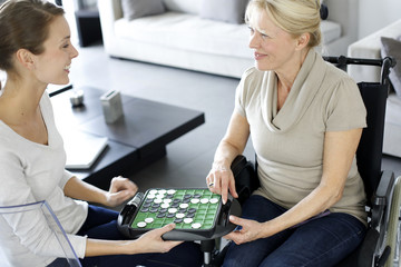 Young homecarer playing game with elderly woman