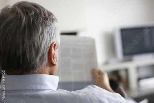 Back view of man reading newspaper at home